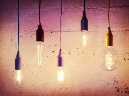 Illuminated light bulbs on concrete wall background. Industrial design. Stock Photo