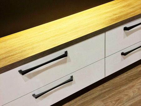 sleek: Chest of drawers with wooden top. Modern furniture.