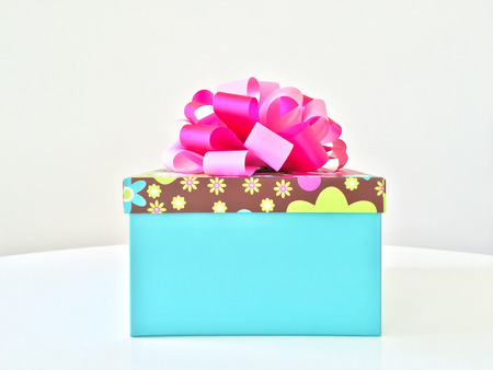 blue gift box: Blue gift box with pink ribbon, on white table.