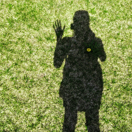 shadow: Shadow of a woman waving her hand, on grass background.