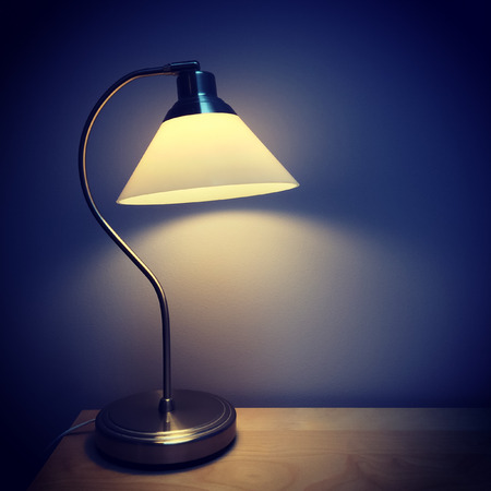 lampshade: Table lamp on a wooden surface in a dark room.