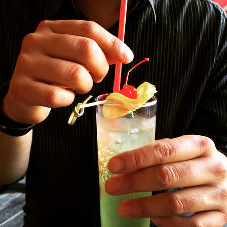 hand holding: Man holding a glass with cocktail, decorated with lemon and cherry.