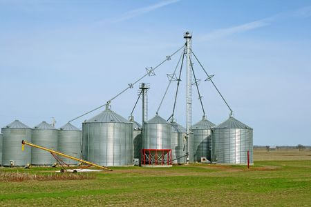 storage bin: Grain silos on a farm in green spring field. Stock Photo