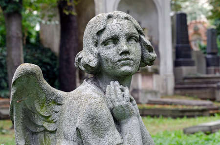 Weathered statue of a praying Angel - tombstone - old Prague cemetery, Czech republic, Europe Stock Photo