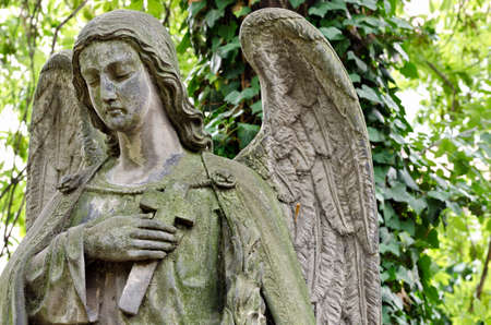 crucifix: Weathered statue of an Angel - tombstone - old Prague cemetery, Czech republic, Europe Stock Photo