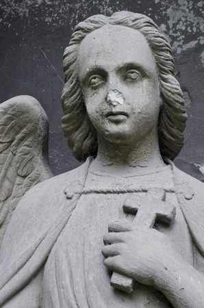 Damaged statue of an Angel with cross - tombstone - old Prague cemetery, Czech republic, Europe