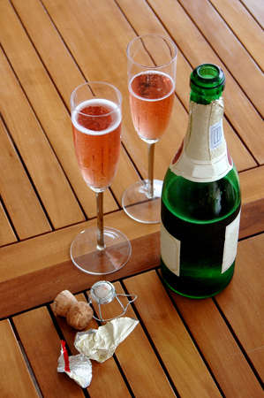 A bottle of red sparkling wine and two champagne glasses on a wooden table outside photo