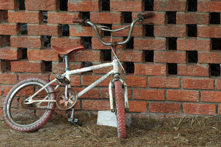 forgotten: An old forgotten child bicycle leaning against a stone wall
