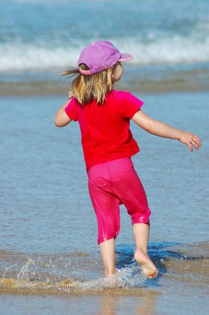 Little happy blond caucasian girl child in pink playing in the water on the beach photo
