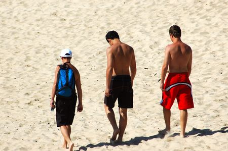 Three young men walking in the sand on the beach photo