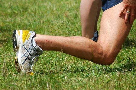 A male leg and arms of an athlete excercising outdoors in nature