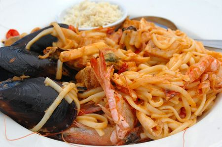 menue: A plate of a delicious and colorful fresh seafood pasta dish with mussels on a white tablecloth Stock Photo