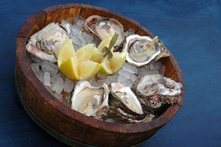 menue: Fresh delicious cape rock oysters on ice with lemon and a fork in a wooden bowl on a blue table cloth in a restaurant Stock Photo