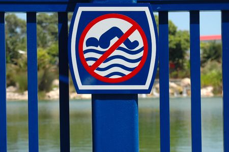A blue metal fence with a no swimming sign in front of a lake Stock Photo - 781413
