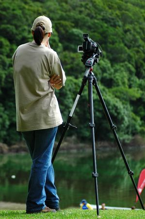 A caucasian woman waiting with a video camera on a tripod to start working in nature