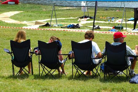 kiddies: A caucasian white family sitting together in chairs outdoors watching an event Stock Photo