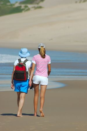 Two young white caucasian women are walking in the sand on the beach together close to the water  photo