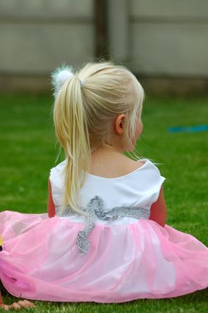 A little white caucasian blond girl with long hair and ponytail in a pink dress sitting on the lawn waiting for her friends  Stock Photo - 806953