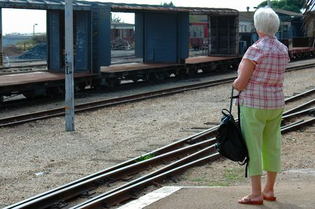 An elderly matured senior white caucasian woman waiting for the train at the railway station outside  photo