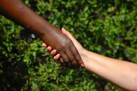 compromising: Handshake between a black hand of an African American woman and a white hand of an caucasian woman holding each other to show there agreement