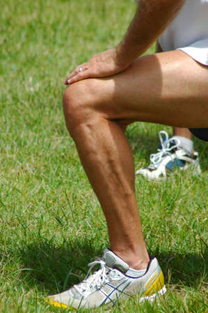 White leg of a caucasian male athlete with hands on knee stretching after excercising outdoors in nature