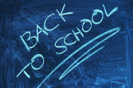 A dirty blackboard in the classroom at school with the message in words BACK TO SCHOOL written with white chalk on it symbolizing the end of the holidays and the start of the new educational term for the students.