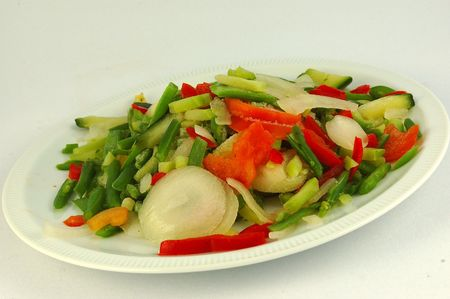 menue: A plate of different frozen healthy colorful vegetables with onions, tomatoes, green and red peppers and beans isolated on white background