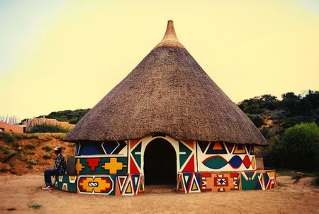 accomodation: A beautiful and colorful African round Ndebele hut in South Africa in the peaceful evening sun