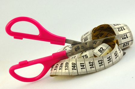 An old used yellow and white measurement in centimeters and millimeters with pink scissors isolated on white background photo