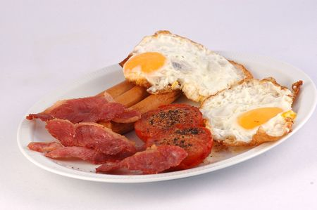menue: Traditional delicious English breakfast: bacon, eggs, sausages and fried tomatoes served on a plate on mothers day isolated on white background  Stock Photo
