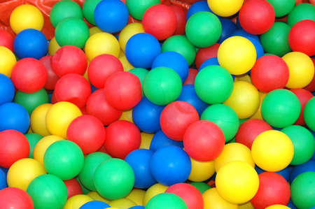 Background closeup of lots of colorful plastic balls in red, yellow, green and blue for kids to play with on the playground outdoors