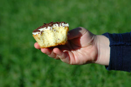 A white little hand of a caucasian child holding and eating a delicious sweet cupcake on a party in the sunshine outdoors  photo