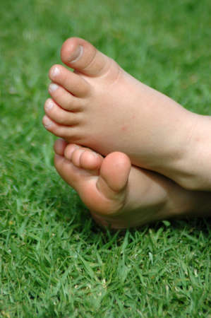 Two little white healthy feet of a caucasian child resting barefeet in the grass of a tidy lawn in the sunshine outdoors during summertime