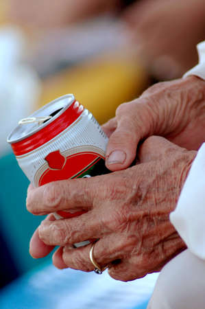 Two wrinkled aged hands of an elderly caucasian white woman holding a can of beer outdoors  photo