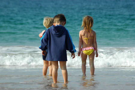 backview: A group of three caucasian white kids (two boys and one girl shown from the back) standing in swimwear in the water of the Indian Ocean and watching out for fish during summertime on a beach in South Africa