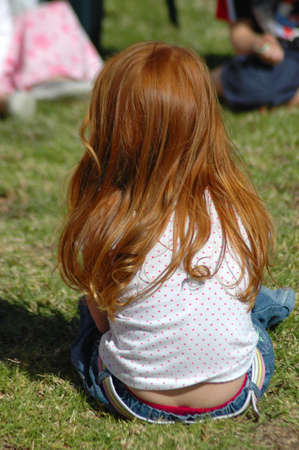 red haired: Back of a caucasian white little girl with beautiful long red hair sitting in the grass on the lawn and watching other kids on the playground outdoors