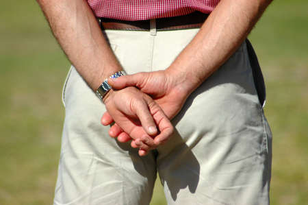 Two white crossed male hands of a caucasian patient referee man standing in the park and waiting for...  photo