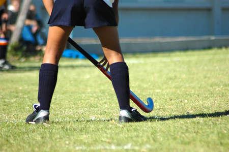 hockey sobre cesped: Las fuertes patas de color blanco de un deportivo caucasian joven jugando Hockey deporte en un equipo al aire libre en un campo