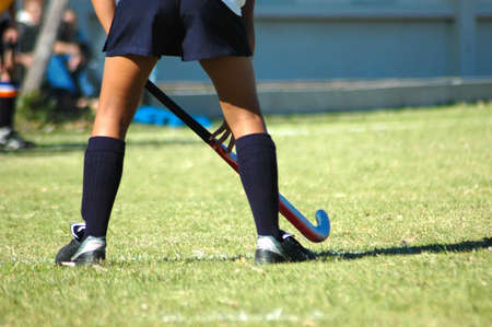 The strong white legs of a sportive caucasian young woman playing Hockey sport in a team outdoors on a field  photo