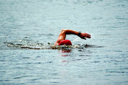 triathlete: A white arm of a caucasian swimmer athlete swimming in the lake
