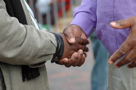 Two African American men shaking their black hands as a sign of big friendship and to welcome  photo