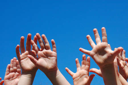 raising hand: Lots of little hands of caucasian white children raising up their arms into the blue sky outdoors  Stock Photo