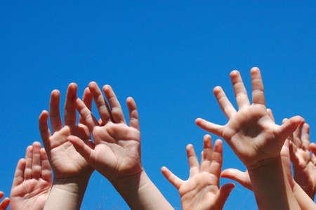 hands free: Un mont�n de peque�as manos de ni�os blancos caucasian elevar sus armas hacia el cielo azul al aire libre  Foto de archivo