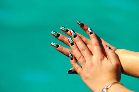The caucasian white hands of a female South African Rugby supporter in front of blue background. Her finger nails are painted in the colors of the national flag of the Rainbow Nation, South Africa, by a professional nail technician Stock Photo - 2056756