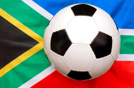 A traditional black and white soccer ball (focus on ball) on national flag background of the rainbow nation South Africa - the host country of the football world cup in 2010