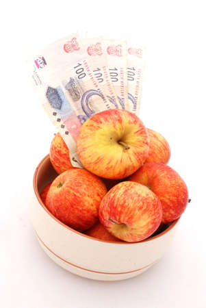 A big bowl full of red apples and four one hundred Rand bills of South African money. Image isolated on white background photo