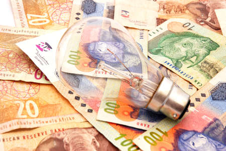 A new light bulb on South African money background photo
