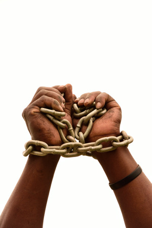 Two chained black male hands of a young South African Xhosa imprisoned man isolated on white studio background. photo