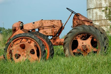 Vintage farm tractor sits next to the grain silo in the field it once worked in Kentucky, USA. photo