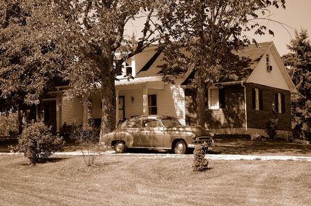 Invoking memories of the 1940s, a sepia image of an antique car parked in front of a country style house in rural Kentucky, USA.